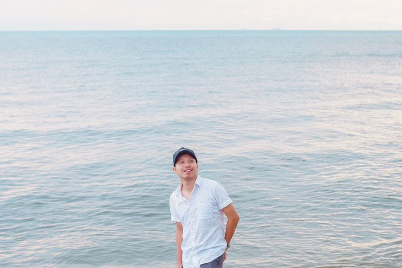 Smiling man looking away while standing against sea