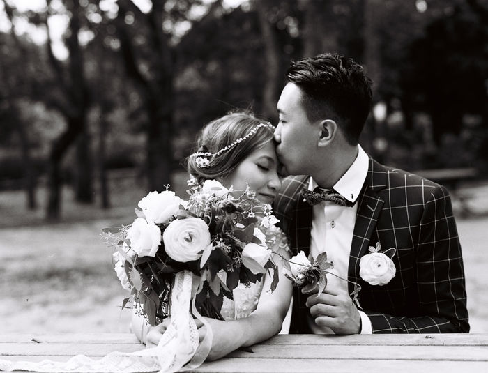 Groom kissing on bride forehead against trees