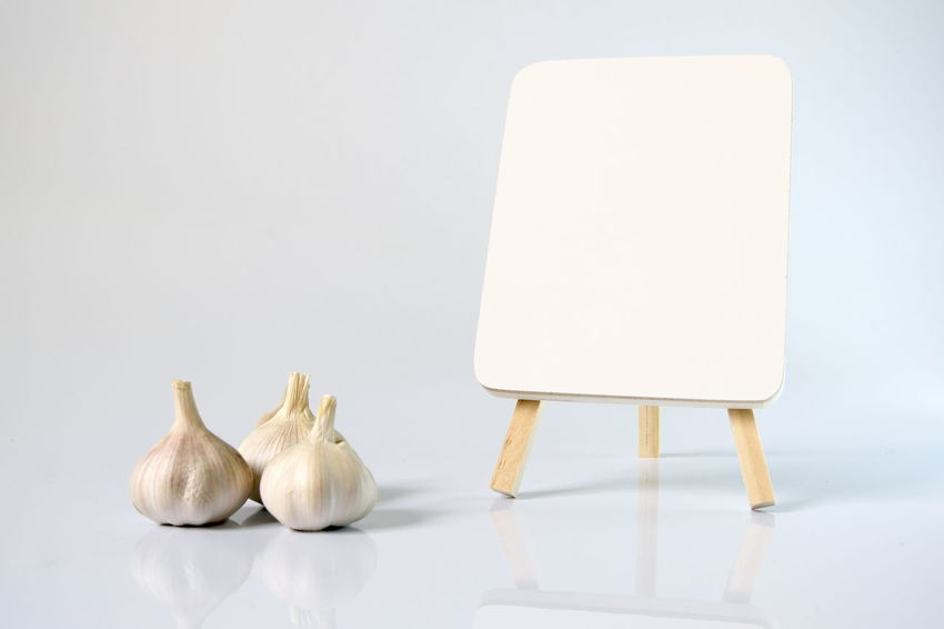 Garlic and blank white board over a white background Blank Cooking Copy Space Day Food Food And Drink Freshness Freshness Garlic Herb Indoors  Ingredient No People Spice Studio Shot White Background White Board White Color