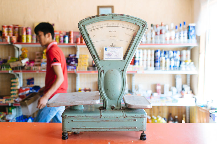 Weighing Scale Against Of Man Standing In Store