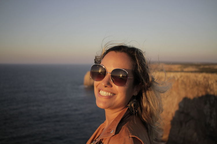 Portrait Of Smiling Woman Wearing Sunglasses By Sea