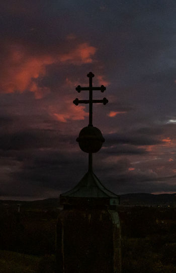 Silhouette cross against dramatic sky during sunset