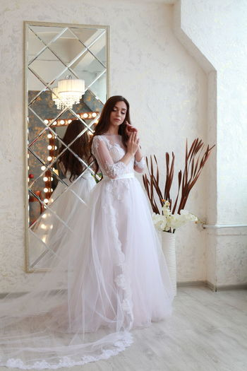 One Person Bride Celebration Newlywed Wedding Dress Portrait Young Adult Looking At Camera Wedding Beautiful Woman Women Adult Real People Beauty Full Length Smiling Young Women Life Events Indoors  Happiness Fashion Hairstyle Flower Arrangement Bouquet