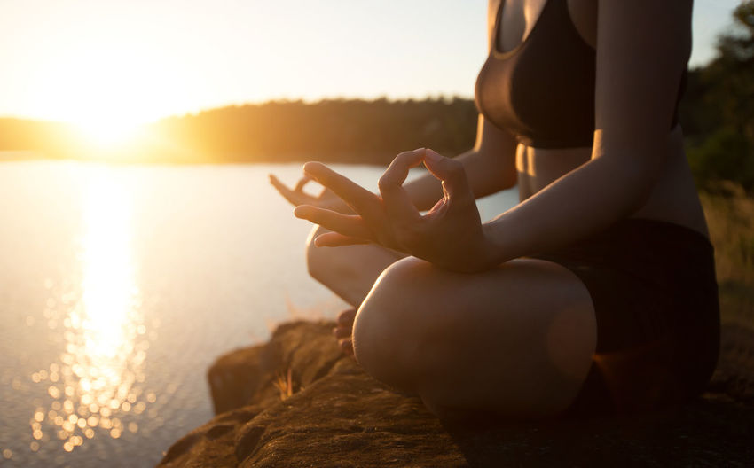 Low section of woman meditating while sitting on rock at lakeshore during sunset