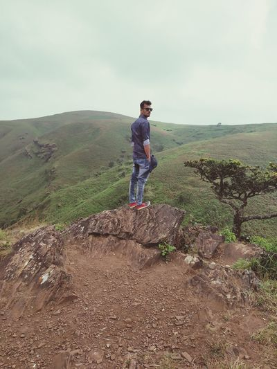 Full length of young man standing on mountain against sky