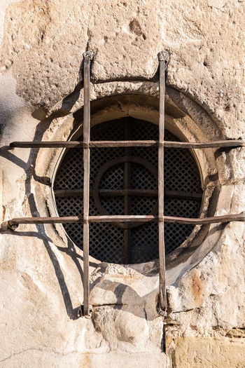 Old historical building with a lattice made of steel in front of the round window Architecture Built Structure Wall - Building Feature No People Building Exterior Metal Day Hole Grid Grate Close-up Window Security Wall Solid Outdoors Geometric Shape Safety Metal Grate Protection Stone Wall