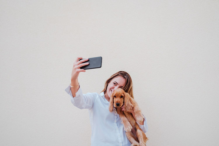 Woman photographing with mobile phone against wall