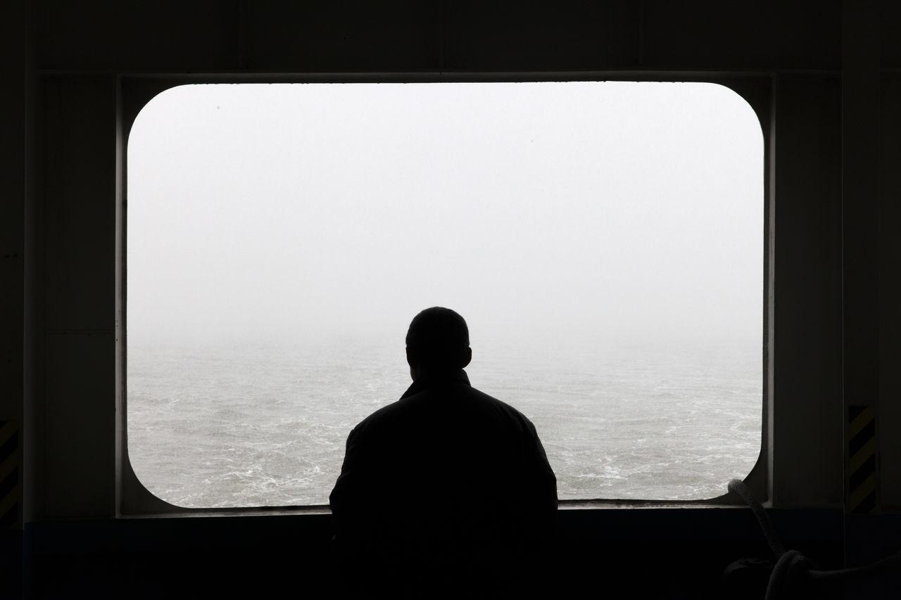Man looking through window of boat