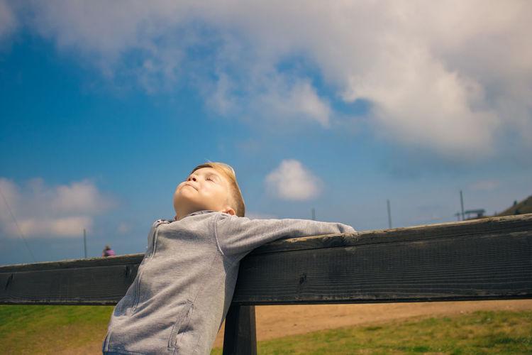 Boy leaning on railing against sky
