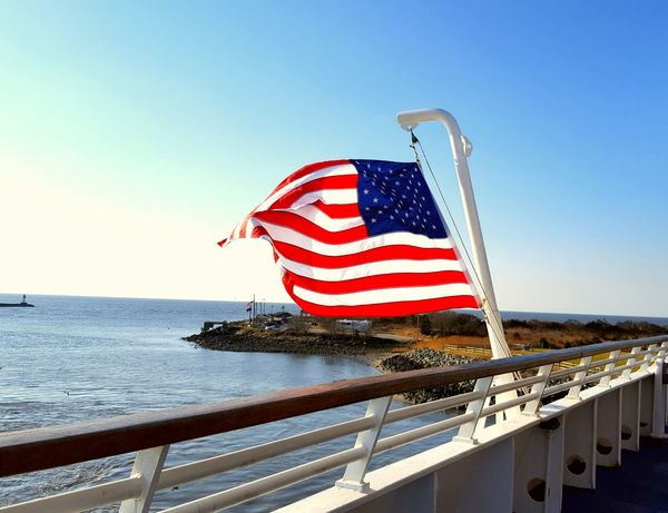 Flag Patriotism Water Outdoors Stars And Stripes Clear Sky Day No People Ferry Boat