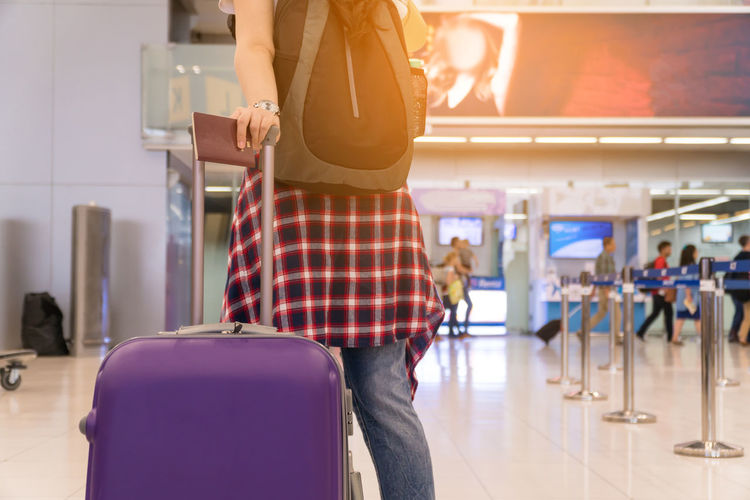 Midsection Of Woman With Luggage Walking At Airport