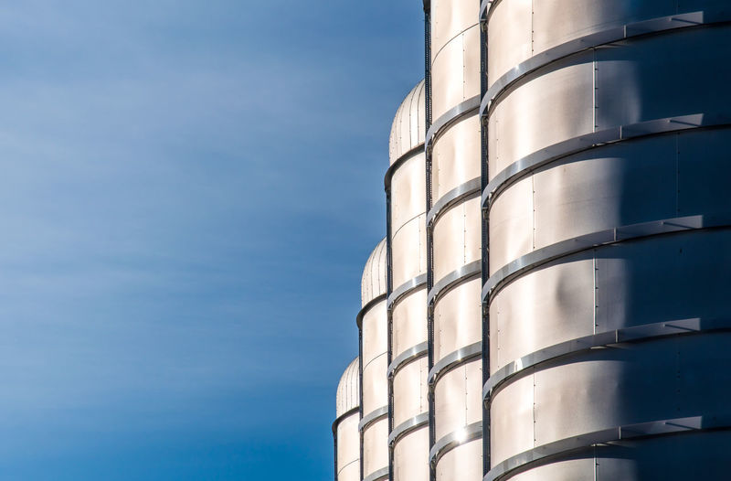 Low angle view of storage tanks against blue sky