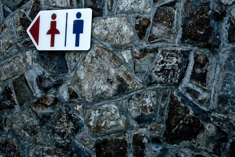 Low angle view of restroom sign on stone wall