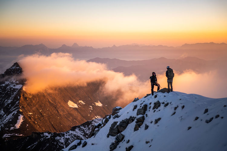 People standing on snowcapped mountain against sky during sunrise