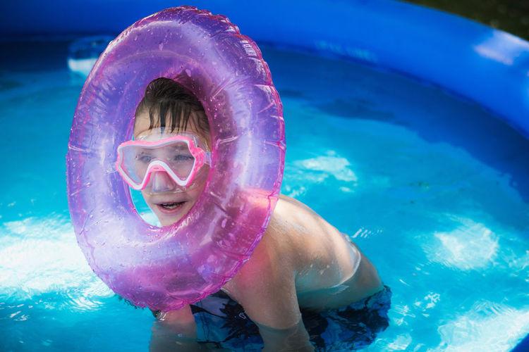 Shirtless boy swimming in wading pool