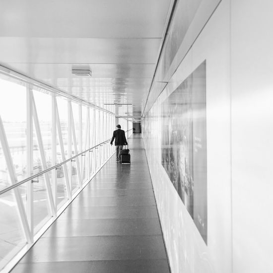 Rear View Of Businessman Walking In Airport Terminal