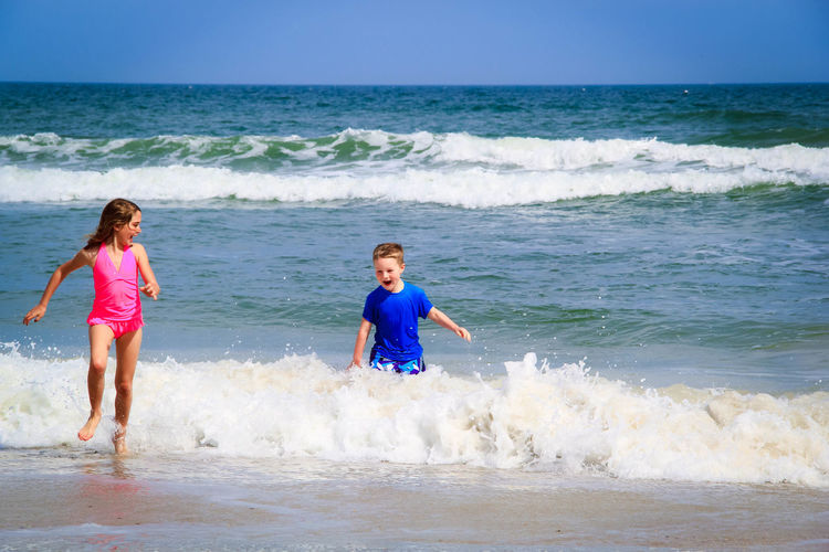 playing in the waves Beach Blue Boy Children Girl Ocean Playing Siblings Water Waves Wet