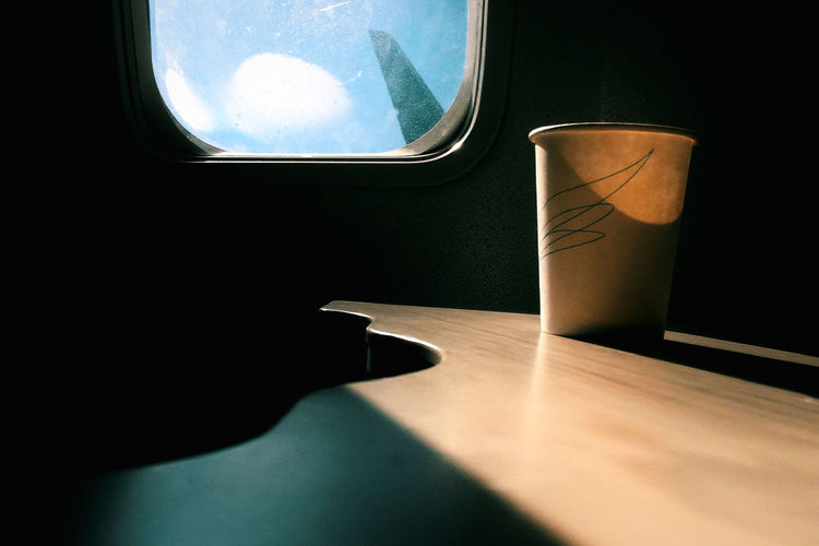 Cropped image of airplane on table against window