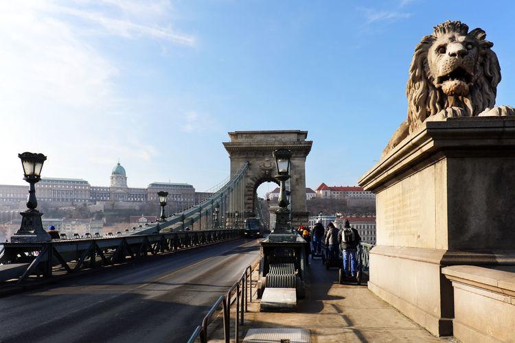 Statue over bridge against sky