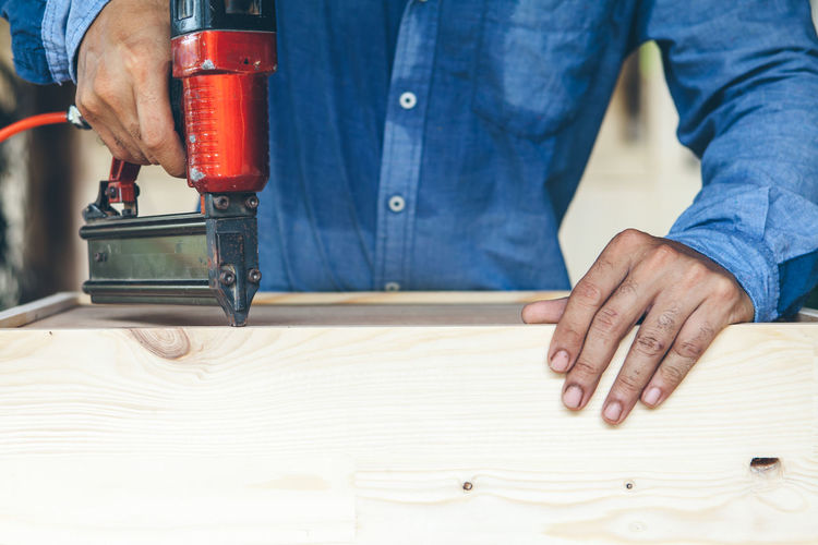 Midsection of man working on cutting board