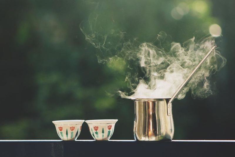 Smoke Emitting From Metal Container By Tea Cups On Railing
