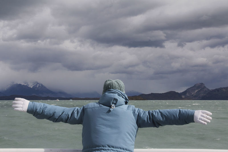 Cloud - Sky Rear View Sky Water One Person Scenics - Nature Real People Beauty In Nature Tranquil Scene Nature Mountain Leisure Activity Lifestyles Non-urban Scene Day Standing Warm Clothing Outdoors Human Arm Joy Adventure