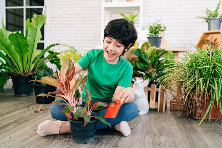 Boy sitting on potted plant in yard