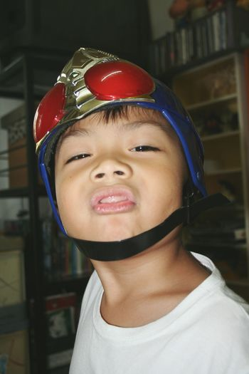 Close-up portrait of boy wearing helmet at home