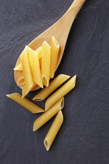 Close-up of penne in wooden spoon on slate