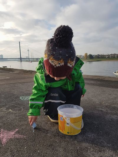 Drawing River Toddler  Childhood Child Silhouette Growing Up Clear Sky Warm Clothing Hat Tree Pavement Drawing Happiness The Week On EyeEm EyeEm Best Shots Autumn Outdoors Skyline Cityscape Shore Boats Chalk Art Crayons Bank Riverside Stories From The City