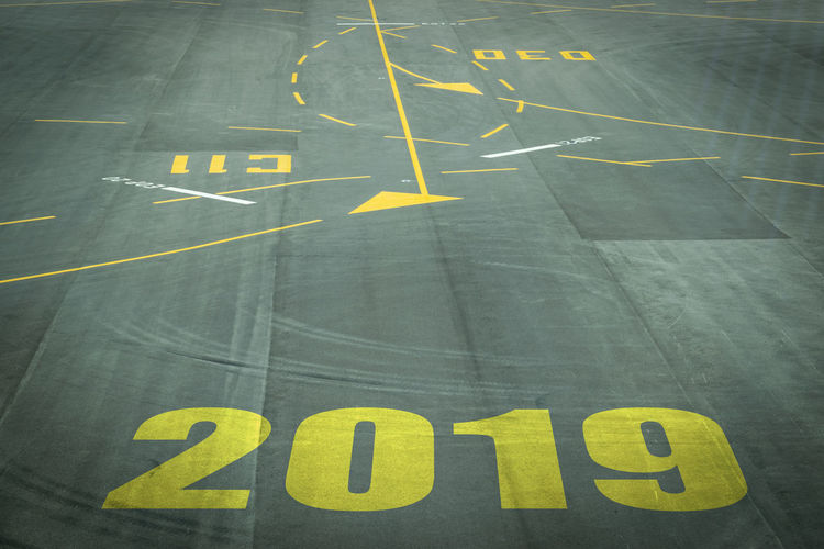 Closeup 2019 figures on the surface of the airport runway texture background. Aerospace Industry Airport Airport Runway Arrow Symbol Communication Day Direction Guidance High Angle View Marking No People Number Outdoors Road Road Marking Sign Symbol Text Transportation Western Script Yellow
