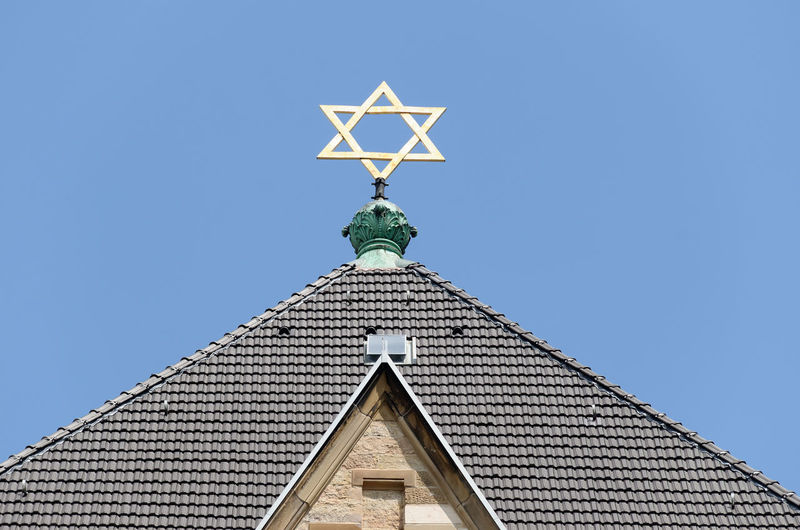 Low angle view of synagoge with star of david against blue sky