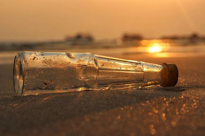 Close-up of glass bottle on shore at beach against sky during sunset