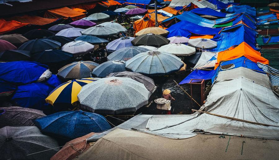 High angle view of colorful parasols at market during rainy season