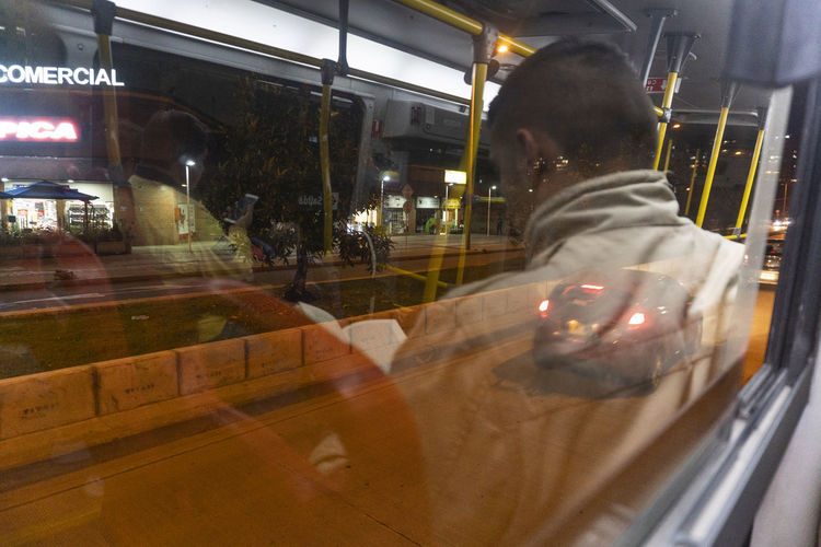 Transportation Mode Of Transportation Real People Motion Glass - Material Illuminated Blurred Motion Transparent One Person Land Vehicle Night Men Reflection Public Transportation City Window Architecture Travel Lifestyles
