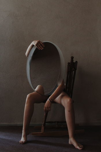 Low section of naked woman holding mirror while sitting on chair in room