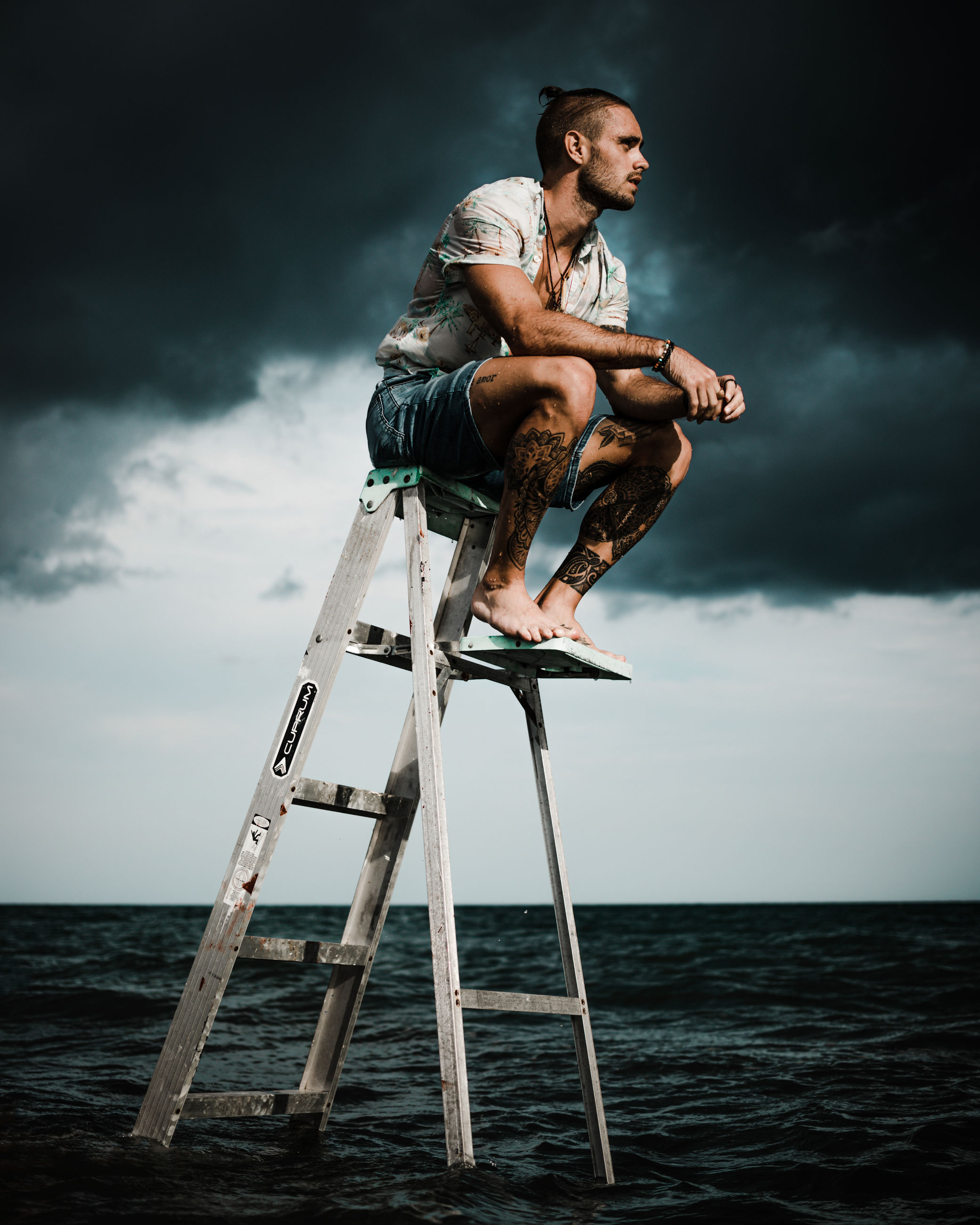 sky, cloud, full length, adult, one person, water, sea, ladder, men, nature, young adult, sitting, blue, activity, land, person, occupation, copy space, sports, beauty in nature, tripod, outdoors