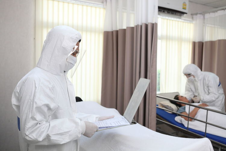Doctor reading medical record while standing in hospital