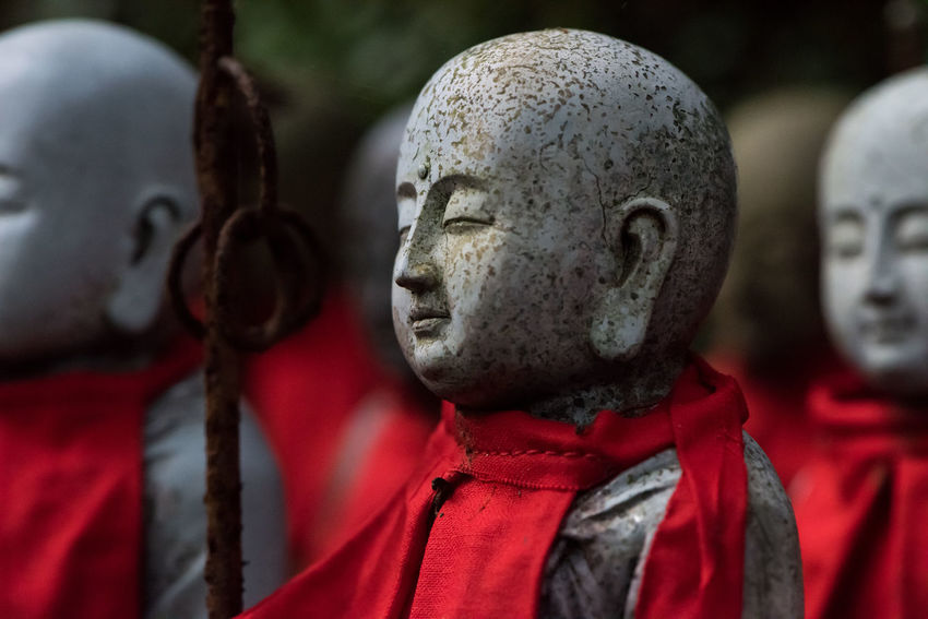 At one of Japan's ancient temples, hundreds of small stone statues stand nobly watching over the ancient grounds buried deep in the mountains, wearing striking red cloaks. ASIA Engyoji Temple Japan Japanese Culture Red Shrine Statue Tradition Buddhism Buddhist Temple Close-up Crowd Culture Religion Scarf Stone Temple