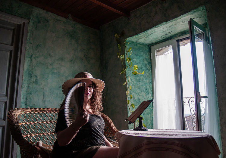 Portrait Of Woman Holding Hand Fan While Sitting By Table At Home