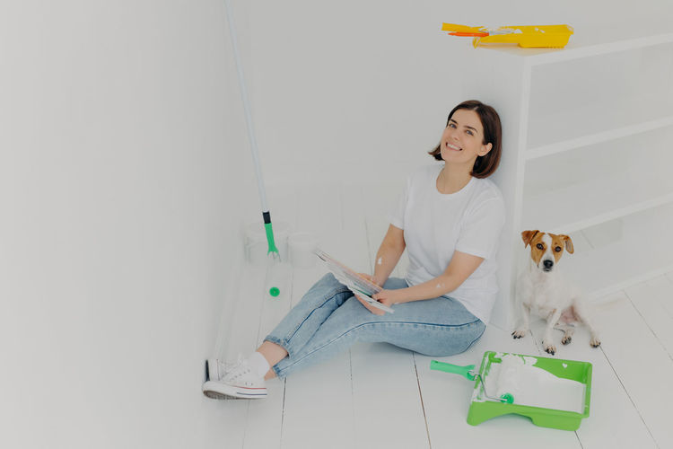 Full length of woman holding color swatch sitting on floor with dog at home