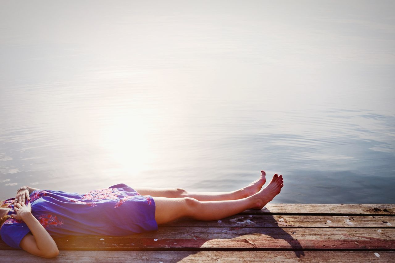 Low section of woman relaxing on wooden pier against water