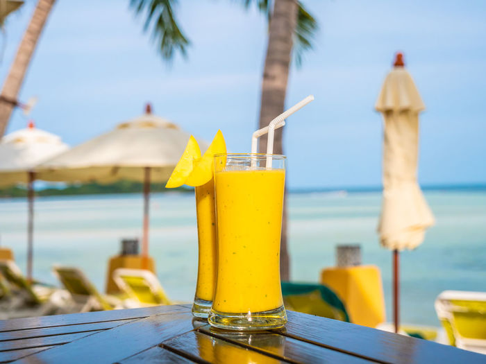 Yellow drink in glass on table against sea