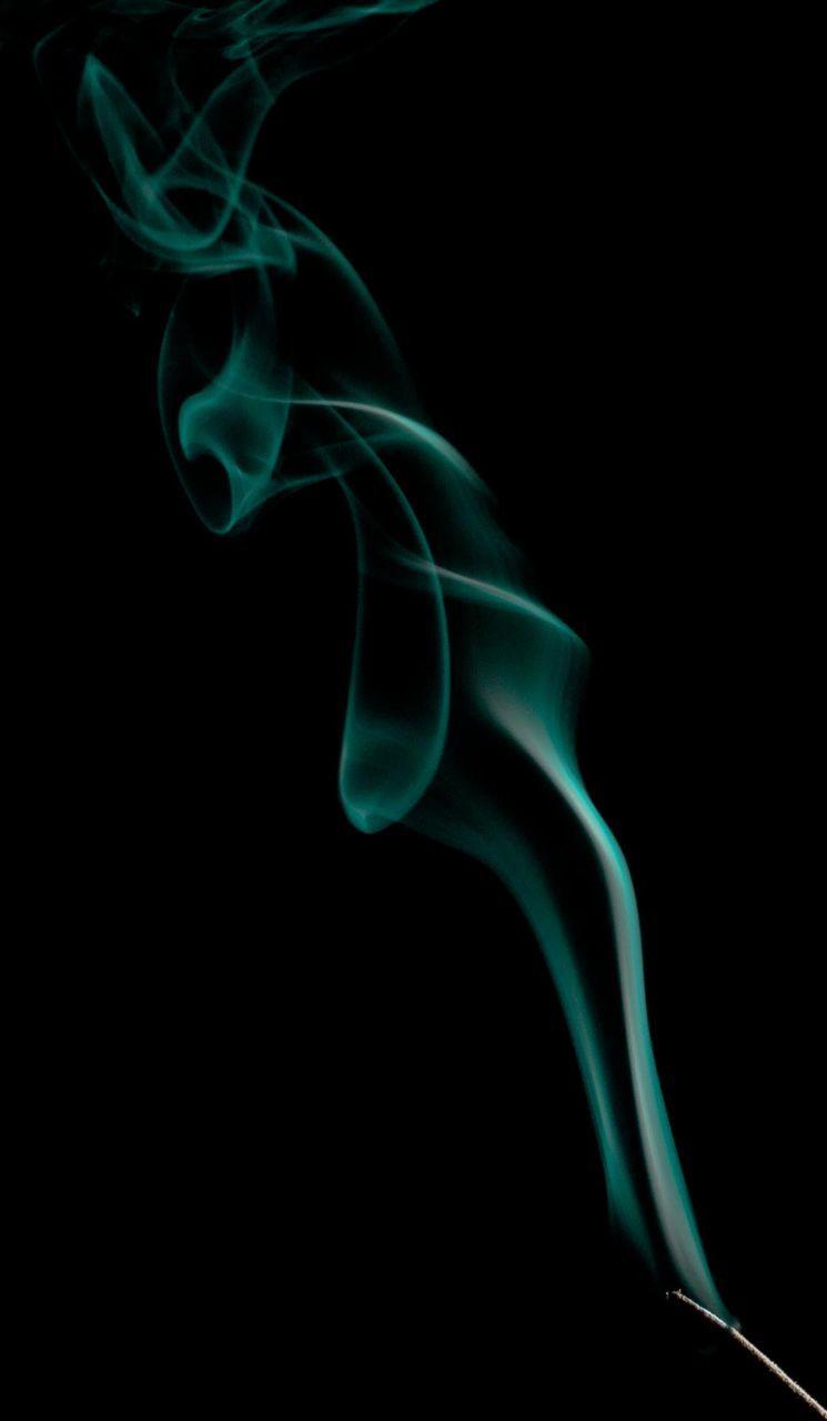 Incense Stick Emitting Smoke Against Black Background