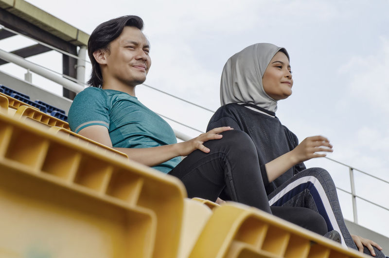 young couple sit in stadium with happy face expression, having fun and cheering to their team Sitting Two People Young Adult Young Men Real People Leisure Activity Casual Clothing Lifestyles Three Quarter Length Men Togetherness Smiling Looking Away Young Women People Adult Day Happiness Looking Emotion Couple - Relationship Contemplation