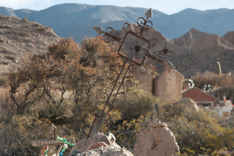 Metallic cross on tombstone against mountains