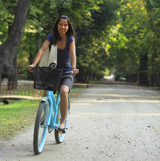 Woman cycling in a park of a city. City Exercise Transportation Woman Bicycle Cheerful Cycling Front View Girl Leisure Activity Lifestyles Mode Of Transport Nature One Person Outdoors Park Real People Ride Riding Smiling Transportation Urban Urban Cycling Urban Transportation Young Adult