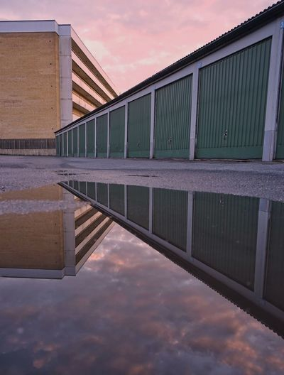 Reflection of building in puddle against sky