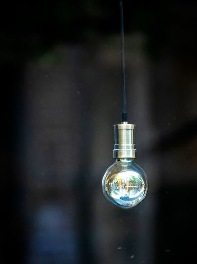 Close-up of light bulb hanging from water