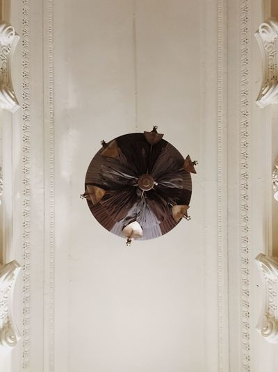 Low angle view of decoration hanging on ceiling against wall